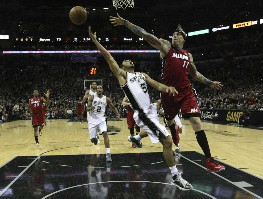 Spurs' Cory Joseph (05) gets fouled as he makes a layup against Miami's Chris Andersen (11) during the second half of Game 3 of the NBA Finals at the AT&T Center on Tuesday, June 11, 2013. (Kin Man Hui/San Antonio Express-News)