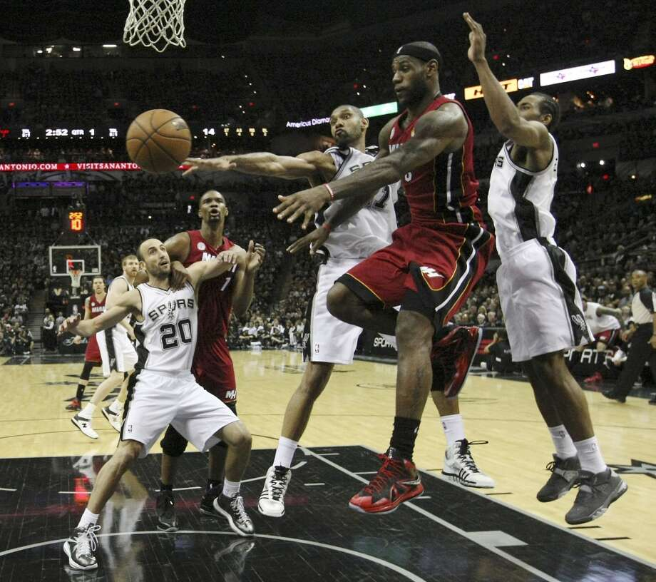 Miami's LeBron James (06) dishes off the ball while under pressure from Spurs' Tim Duncan (21) and Kawhi Leonard (02) during the first half of Game 3 of the NBA Finals at the AT&T Center on Tuesday, June 11, 2013. (Kin Man Hui/San Antonio Express-News)
