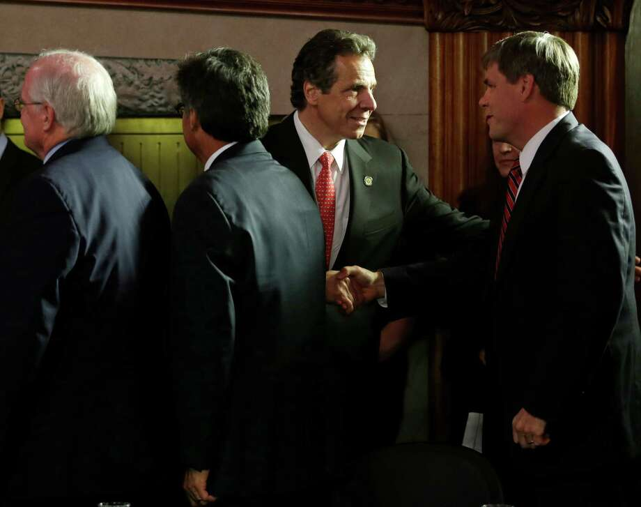 New York Gov. Andrew Cuomo, center, shakes hands with Greene County District Attorney Terry Wilhelm in the Red Room at the Capitol on Tuesday, June 11, 2013, in Albany, N.Y. Senate Republicans remain strongly opposed to creating a voluntary system of taxpayer-funded election campaigns that's getting a strong, last-minute push by some Democrats. Cuomo and the Assembly Democrats support public financing as part of a package of new laws to require greater disclosure and lower donation limits. (AP Photo/Mike Groll) Photo: Mike Groll