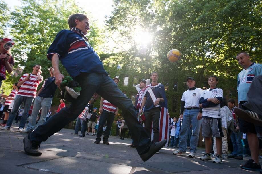 USA fans kick around a soccer ball in Occidental Park before the USA Men's National Team's World Cup Qualifier against Panama at Century Link Field in Seattle, WA on June 11, 2013.