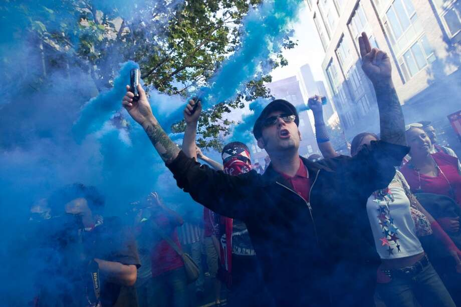 USA fans light blue smoke bombs during a march from Occidental Park to Century Link Field before the USA Men's National Team's World Cup Qualifier against Panama in Seattle, WA on June 11, 2013.