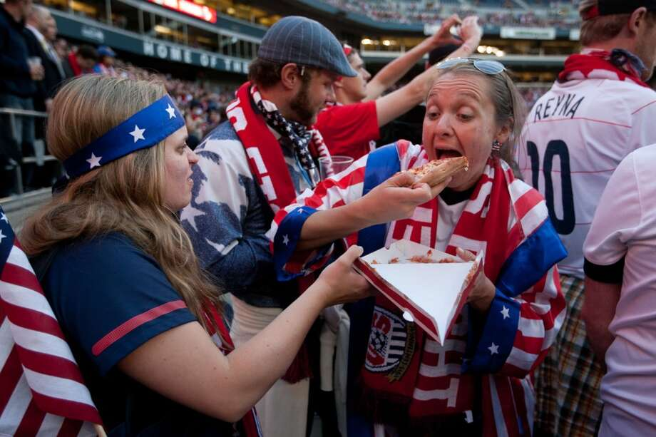 USA fan Molly Malone of Vancouver shares a slice of pizza with her sister Jessica Malone of Denver, while watching the USA Men's National Team's World Cup Qualifier against Panama at Century Link Field in Seattle, WA on June 11, 2013.