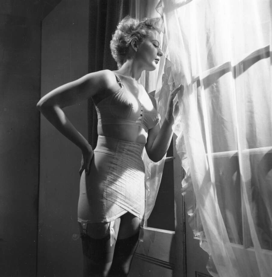 Model Claudia Kerr wears a corset in 1953. Completely boneless and made of light embroidered nylon and elastic net, it was cut 'sarong style' and was guaranteed not to 'ride up'. (Photo by Bert Hardy/Getty Images)