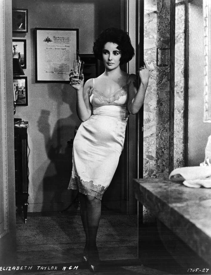British-born actress Elizabeth Taylor stands in a doorway and wears slip as she holds a glass in a still from the film, 'Butterfield 8' directed by Daniel Mann, 1960.
