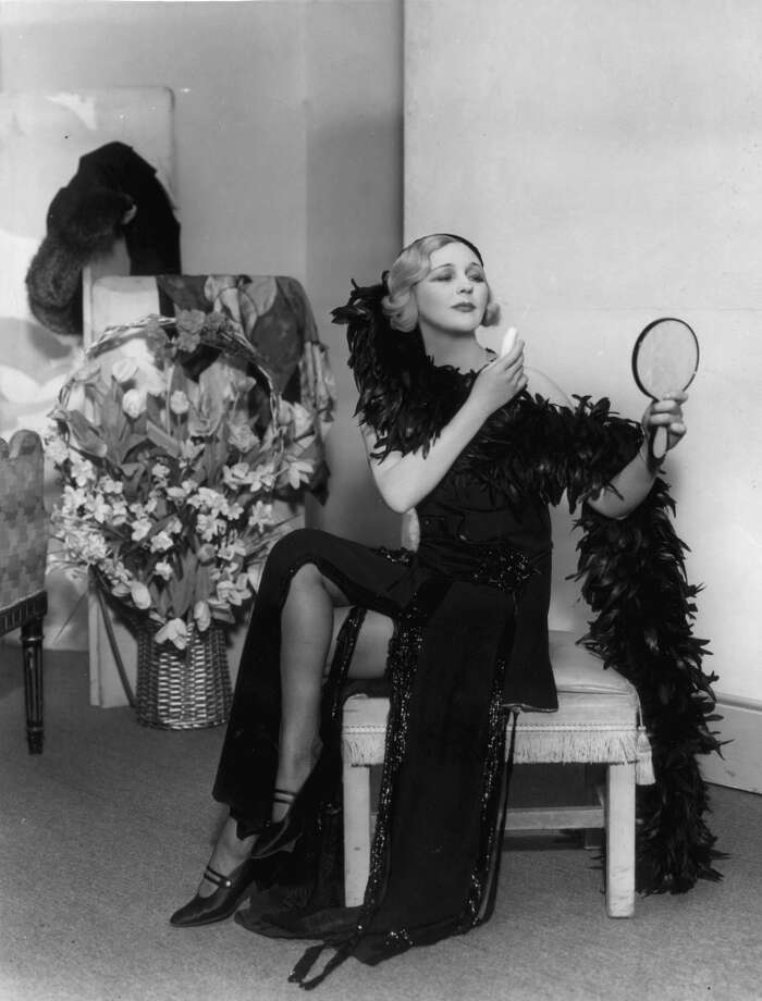 March 1933:  A woman sensationally dressed in a feather boa and beaded gown applies her make-up in a scene from 'Gay Love' at the Lyric Theatre, London.