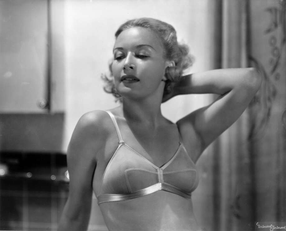 Circa 1935: Portrait of a blonde woman posing in a brassiere.
