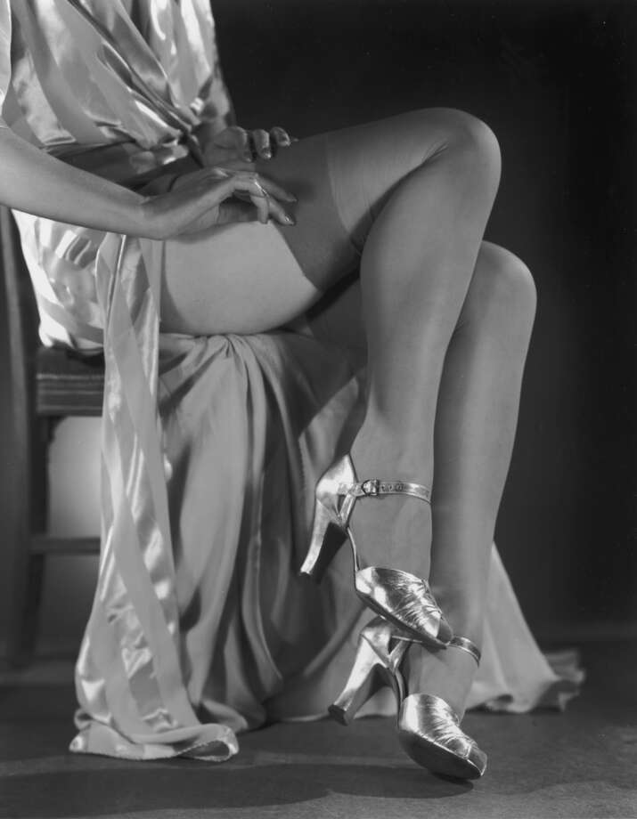 Circa 1940: Closeup of a woman pulling on stockings while sitting in a chair in a silk dressing gown and metallic open-toed heels.