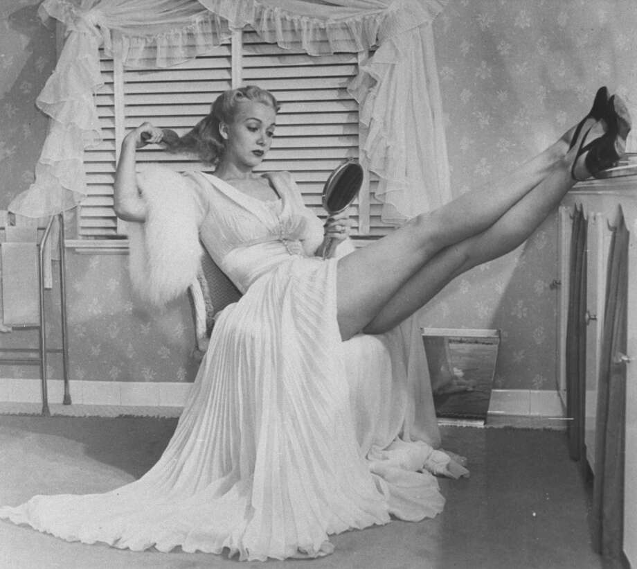 Movie actress Carole Landis clad in negligee as she languidly brushes her hair while showing off her legs.