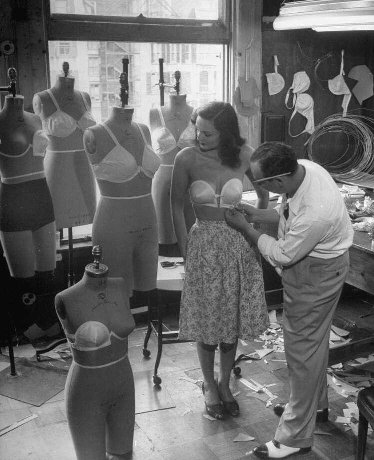 July 1946: Designer Jack Glick fitting a strapless bra on model.