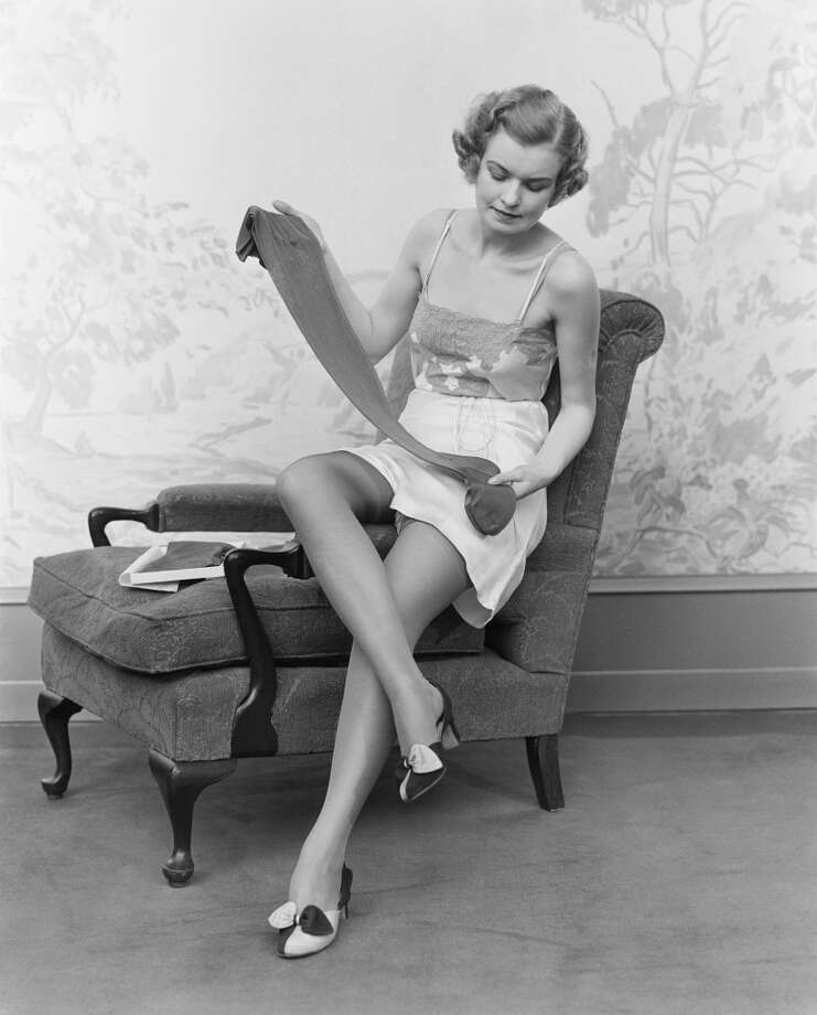 Circa 1930s:  Woman wearing lingerie, sitting on arm of chair, holding up pair of silk stockings.