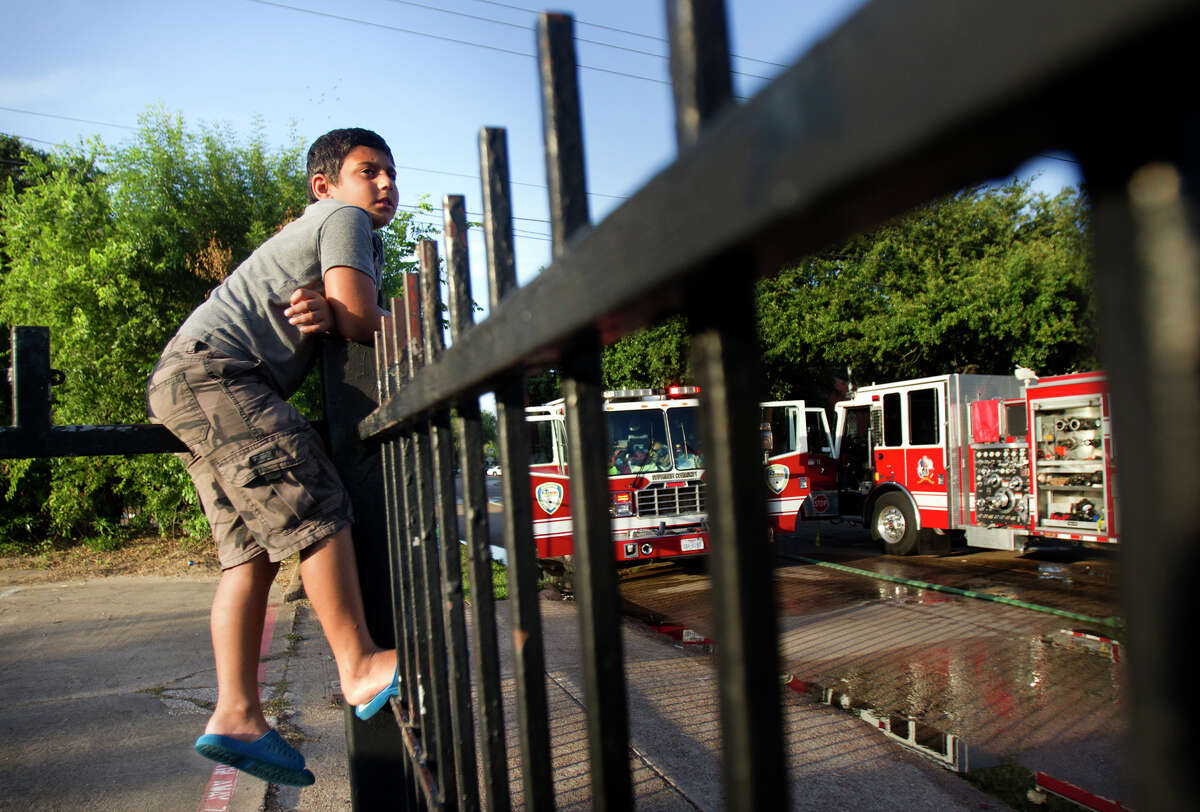 Mushtag Lazim, 8, watches a firefighters work the scene of a 2-alarm fire at an apartment complex on Sapling near Gustine, Wednesday, June 12, 2013, in Houston.