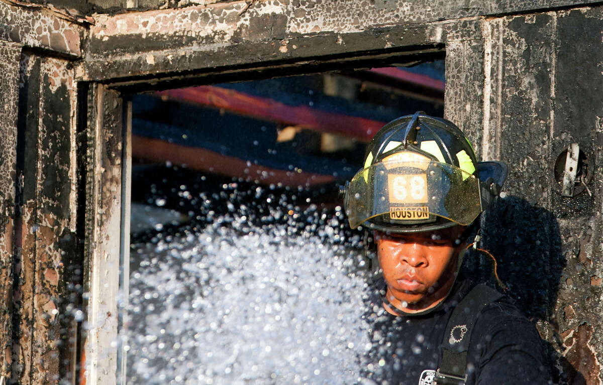 Firefighters work the scene of a 2-alarm fire at an apartment complex on Sapling near Gustine, Wednesday, June 12, 2013, in Houston.