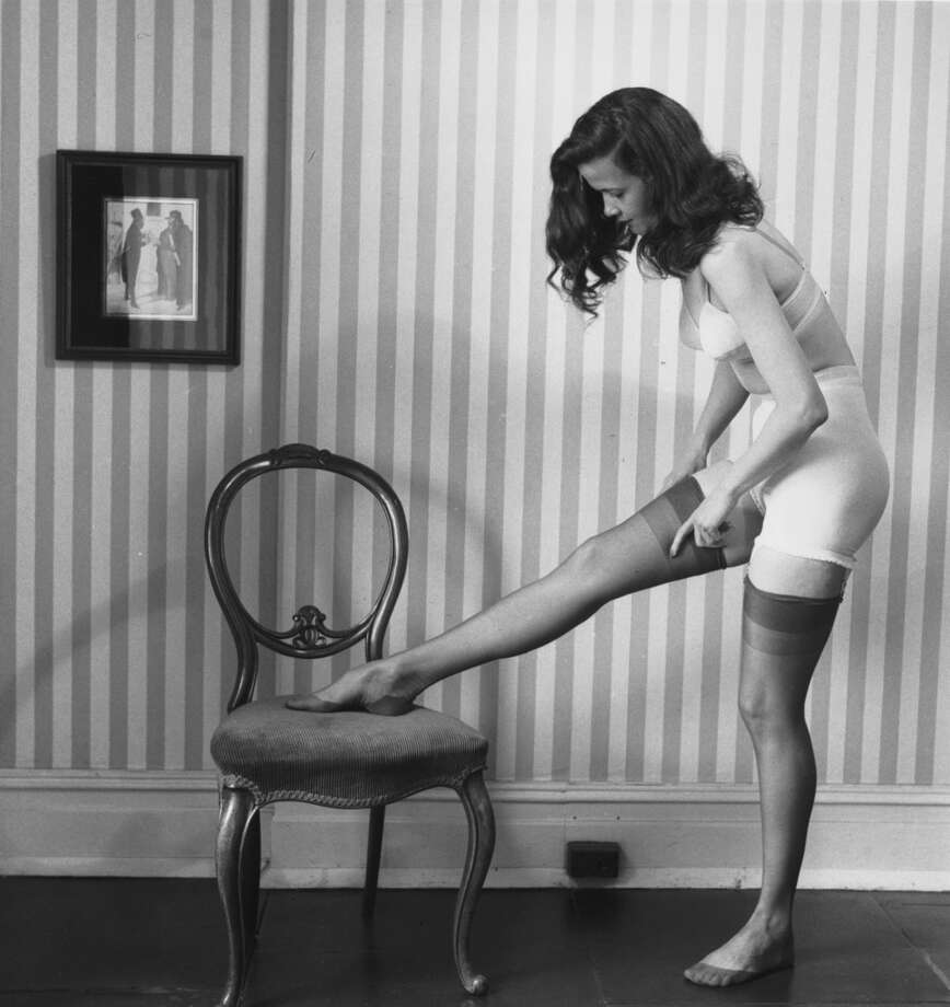 A woman in underwear putting on a pair of stockings in 1949. Her bra is by Warner and her panty girdle is made of net-tex.  Photo by Bill Brandt/Getty Images)