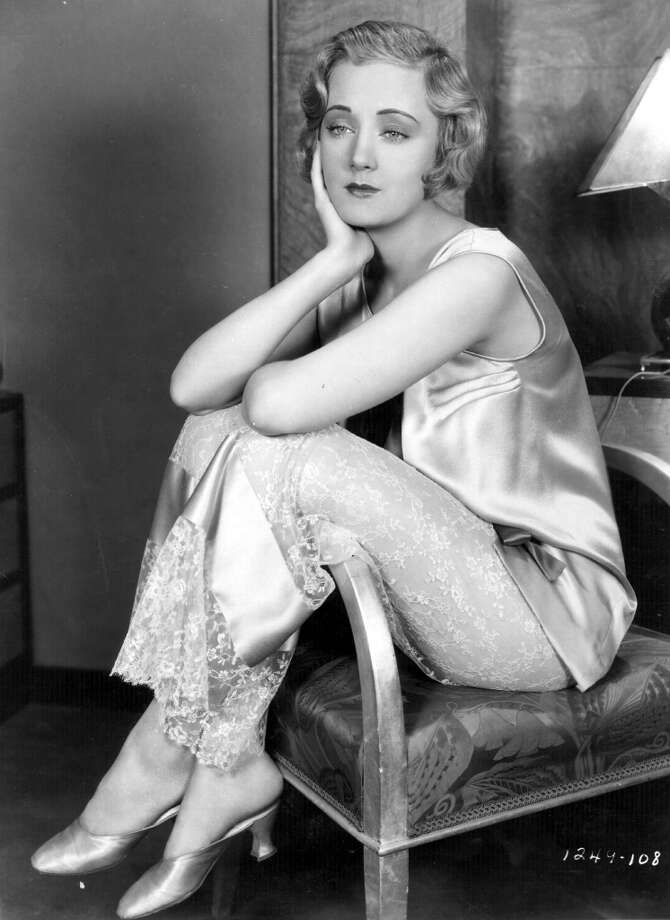 1930:  Actress Josephine Dunn sits with her legs over the arm of her chair in the film 'Safety In Numbers', directed by Victor Schertzinger for Paramount.