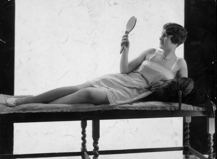 Circa 1924:  Propped up by a cushion, a woman checks her appearance in a hand held mirror.