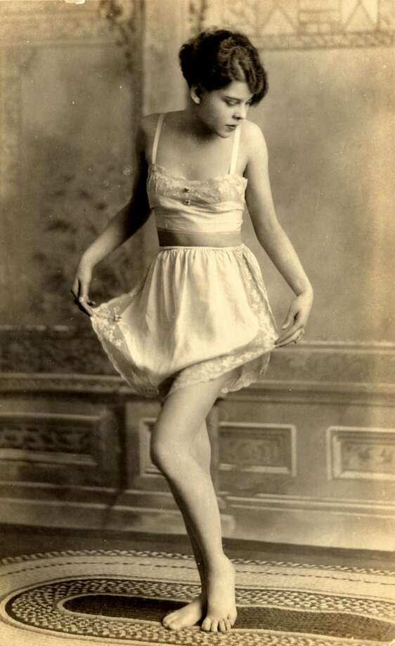 Full-length portrait of a young woman as she stands barefoot on a rug in a bra and half-slip, the lace-edged trim of which she lifts with her hands, 1910s or 1920s.