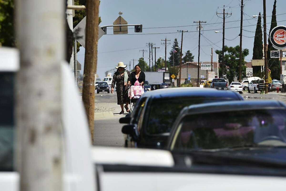 Two women walk along Lassen Avenue, May 21, 2013 in Huron, California. Huron is 98 percent Latino and the fourth-poorest place in California. (Eric Paul Zamora/Fresno Bee/MCT)