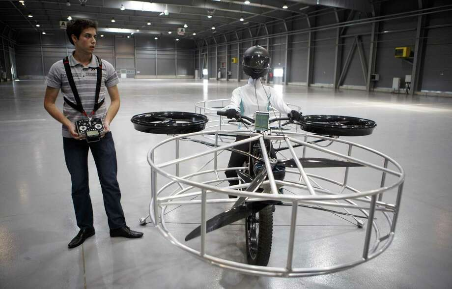 "A technician holds the remote control for a ""Flying bike"" bicycle ahead of its first public flight on June 12, 2013 in Prague, Czech Republic. The bike has been manufactured by 3 different companies from the Czech Republic (Duratec, Technodat, Evektor) and has been supported by French Company Dassault System. The F-Bike has four main motors and two stabilization motors. It has an estimated constant flight time of 3-5 minutes. Photo: Matej Divizna, Getty Images / 2013 Matej Divizna"