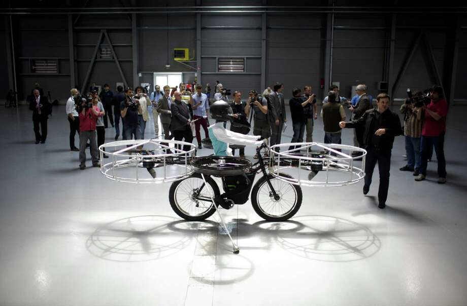 "Journalists look at a ""Flying bike"" bicycle ahead of its first public flight on June 12, 2013 in Prague, Czech Republic. Photo: Matej Divizna, Getty Images / 2013 Matej Divizna"
