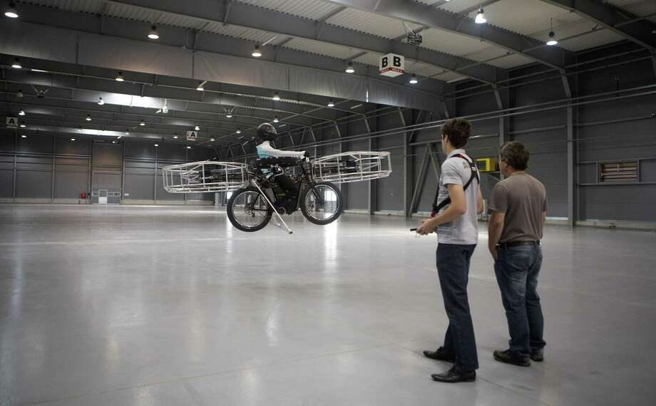 "A technician operates by remote control ""Flying bike"" bicycle ahead of its first public flight on June 12, 2013 in Prague, Czech Republic. Photo: Matej Divizna, Getty Images / 2013 Matej Divizna"