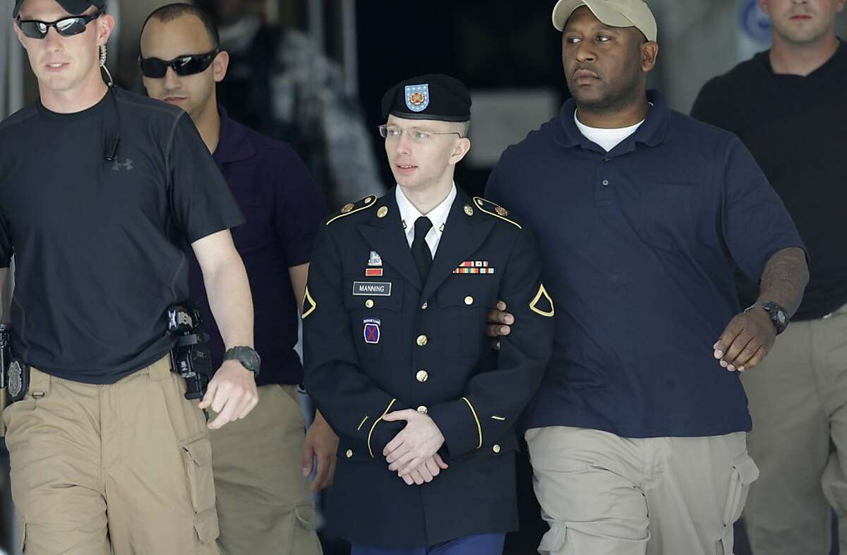Army Pfc. Bradley Manning, center, is escorted out of a courthouse in Fort Meade, Md., Tuesday, June 4, 2013, after the second day of his court martial. Manning is charged with indirectly aiding the enemy by sending troves of classified material to WikiLeaks. He faces up to life in prison. (AP Photo/Patrick Semansky)