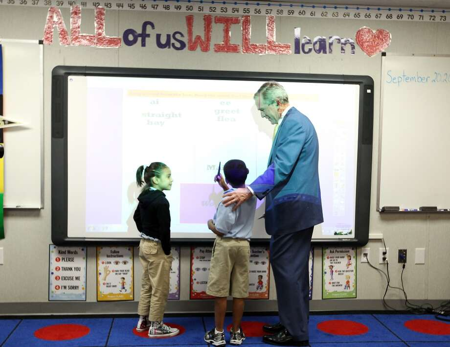 Former President George W. Bush talks with Ashton Drisdale and Mia Ramos, both 7, in Michele Rodriguez's 2nd grade class as he toured KIPP Explore Academy, Thursday, Sept. 20, 2012, in Houston, before meeting with HISD Superintendent Terry Grier, KIPP officials and others to discuss school leadership. ( Karen Warren / Houston Chronicle )