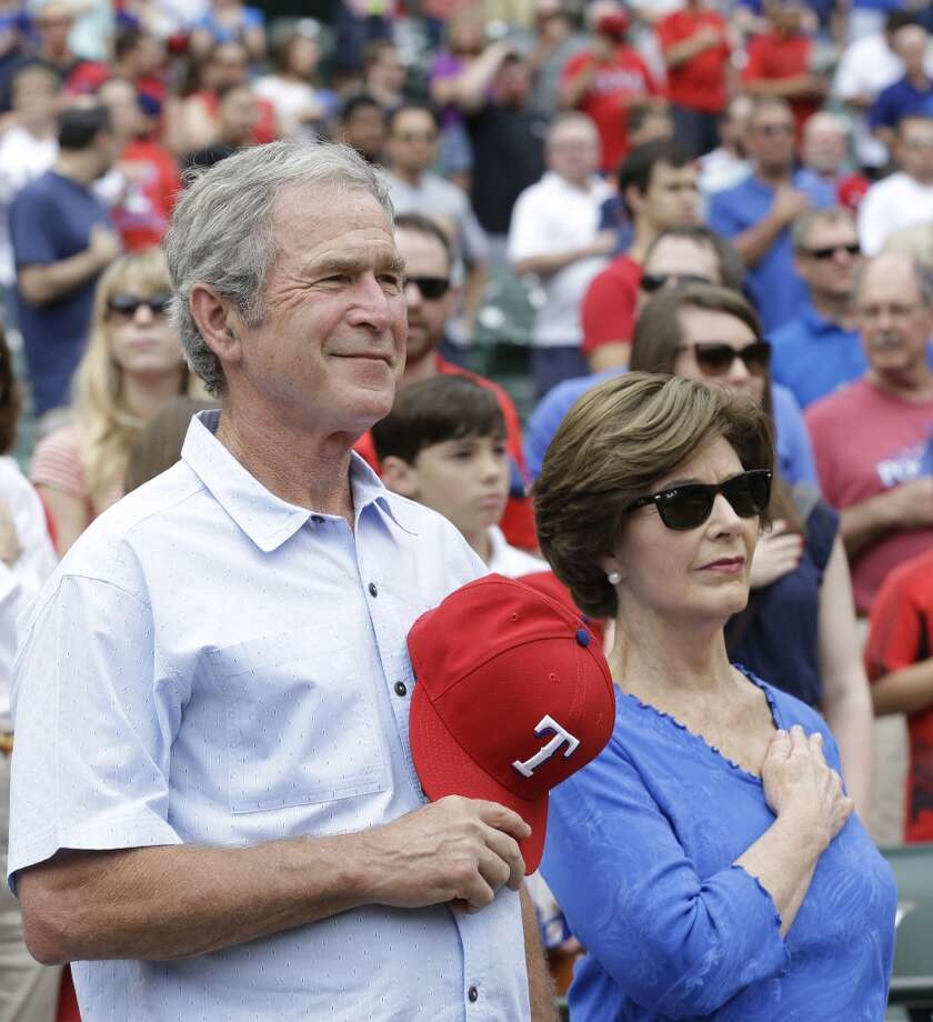 Former President George W. Bush, left, stands during the national anthem with his wife Laura Bush before the the baseball game between the Kansas City Royals  and Texas Rangers Saturday, June 1, 2013, in Arlington, Texas. (AP Photo/LM Otero)