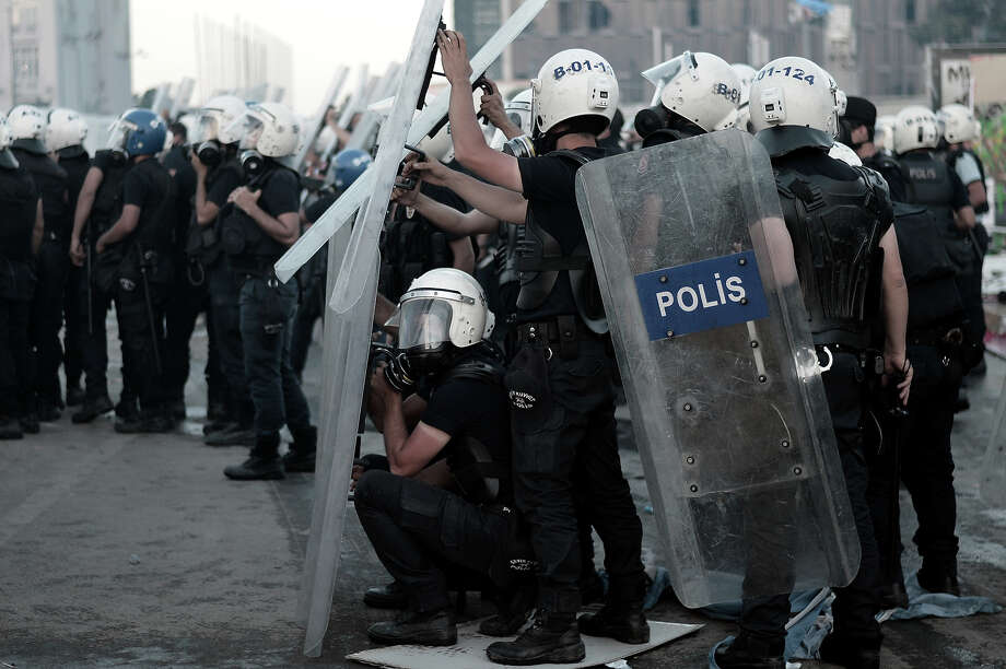 "Riot police clash with protesters on Taksim square in Istanbul on June 11, 2013.  Riot police fired tear gas and rubber bullets to clear protesters from an Istanbul square on June 11 as Turkish Prime Minister Recep Tayyip Erdogan warned he would show ""no more tolerance"" for the unrelenting mass demonstrations against his Islamic-rooted government. Hundreds of police stormed the city's Taksim Square, the epicenter of nearly two weeks of unrest, in the early morning and brought bulldozers to clear the makeshift barriers erected by demonstrators after police pulled out of the area on June 11. Photo: ARIS MESSINIS, AFP/Getty Images / 2013 AFP"