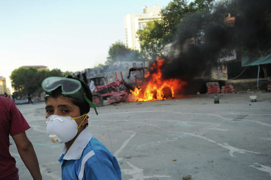 A boy stands near burning road works equipment as Turkish police battle anti-government protestors as they try to reestablish police control of Taksim Square after an absence of 10 days on June 11, 2013 in Istanbul, Turkey. The protest began over the Gezi Park redevelopment project but swiftly turned into a protest and street party aimed at Prime Minister Recep Tayyip Erdogan and what protestors call his increasingly authoritarian rule. The protest has spread to dozens of cities in Turkey, in secular anger against  Mr. Erdogan and his Islam-rooted Justice and Development Party (AKP). Photo: Scott Peterson, Getty Images / 2013 Scott Peterson