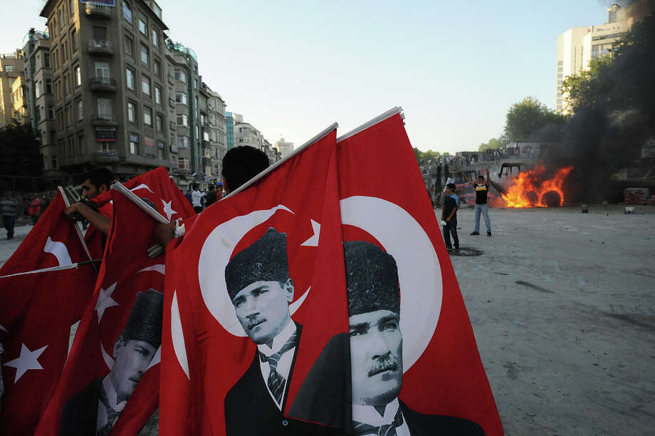 Flags bearing the image of Mustafa Kemal Ataturk are carried near a burning bulldozer,  as Turkish police battle anti-government protestors as they try to reestablish police control of Taksim Square after an absence of 10 days on June 11, 2013 in Istanbul, Turkey. The protest began over the Gezi Park redevelopment project but swiftly turned into a protest and street party aimed at Prime Minister Recep Tayyip Erdogan and what protestors call his increasingly authoritarian rule. The protest has spread to dozens of cities in Turkey, in secular anger against  Mr. Erdogan and his Islam-rooted Justice and Development Party (AKP). Photo: Scott Peterson, Getty Images / 2013 Scott Peterson