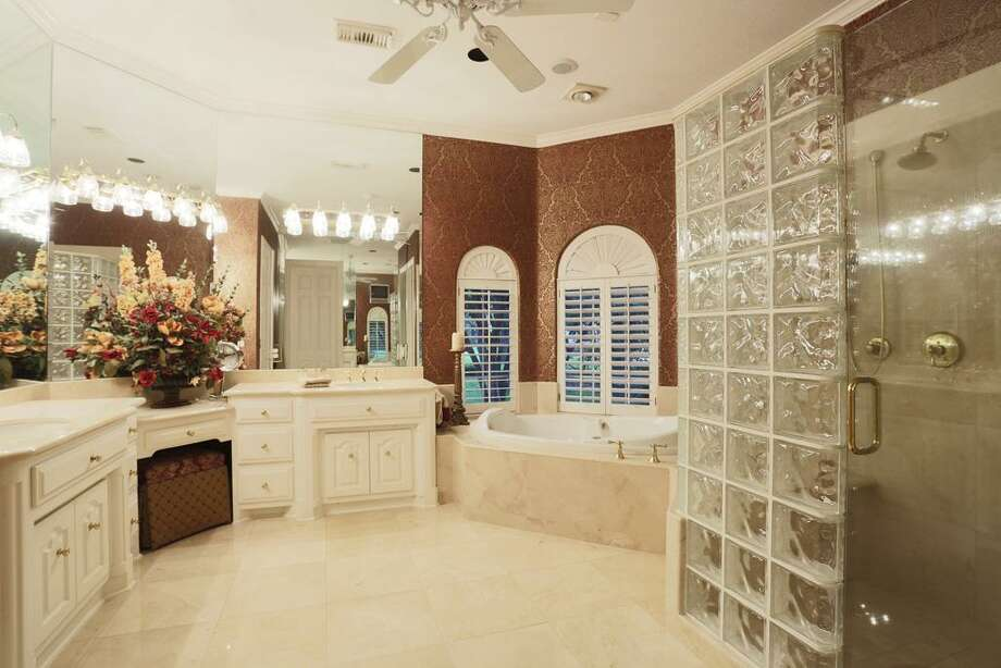 Beautiful Master bath with large walk in shower, jetted bath tub, his and her vanities and dual closets - each with a cedar closet. Photo: HAR