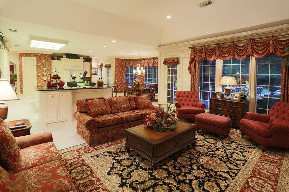 Family room with tile floors, wall of windows overlooking the pool and custom window treatments. Photo: HAR