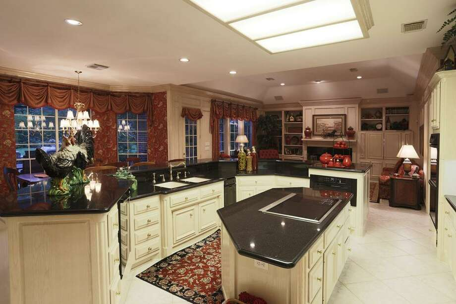 Fabulous gourmet kitchen! Spacious island with cook top, lots of storage and prep space, generous pantry and open view to family room. Photo: HAR