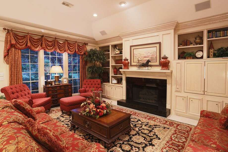 Family room offers a gas fireplace, built in entertainment center and storage/display shelves. Photo: HAR