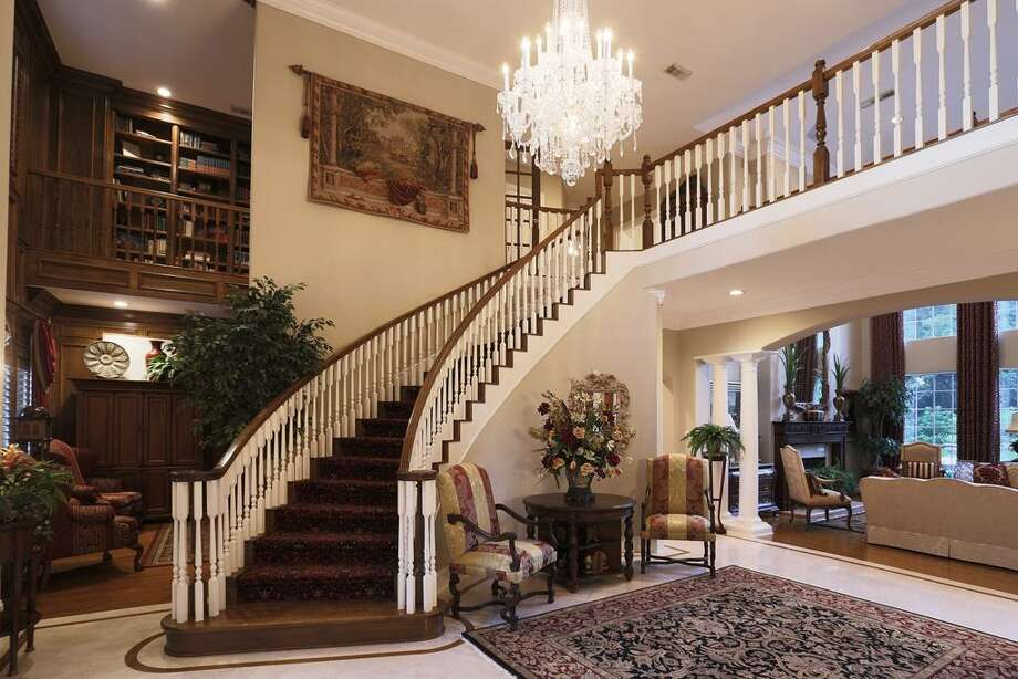 The inviting foyer ushers you into the formal living and dining areas with beautiful pool views Photo: HAR