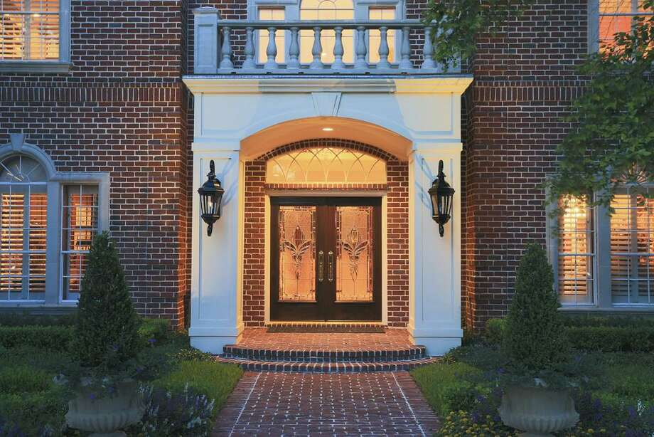 Welcoming approach adjoining the expansive circle drive, stone & stucco detail and double front doors. Photo: HAR