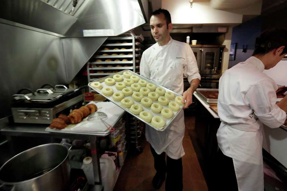 This June 3, 2013 photo shows chef Dominique Ansel, left, making Cronuts, a croissant-donut hybrid, at the Dominique Ansel Bakery in New York. Ansel makes only 200 to 250 Cronuts every morning and has been selling out within an hour. (AP Photo/Richard Drew)