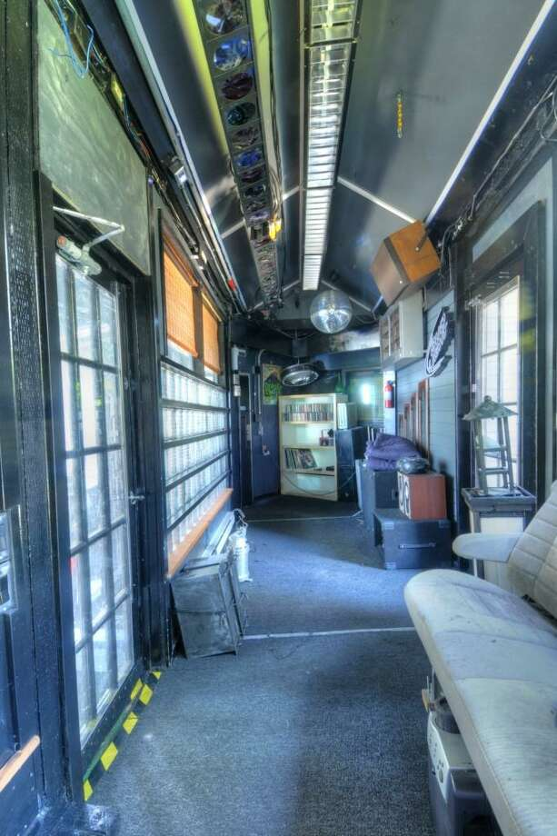 """Private nightclub"" of 144 N.W. 103rd St., in Greenwood. The 510-square-foot house, built in 1926, has one bedroom, a three-quarter bathroom, a 16-camera surveillance system, three electrical subpanels, a gray-water well, a mirrored bedroom and wooden walkways on a 5,100-square-foot lot. It's listed for just $199,950, although the owner's ""huge collection"" of audio, lighting and electrical supplies are available for a ""small added cost."" Photo: Marc Boyd, Sound Point Real Estate LLC"