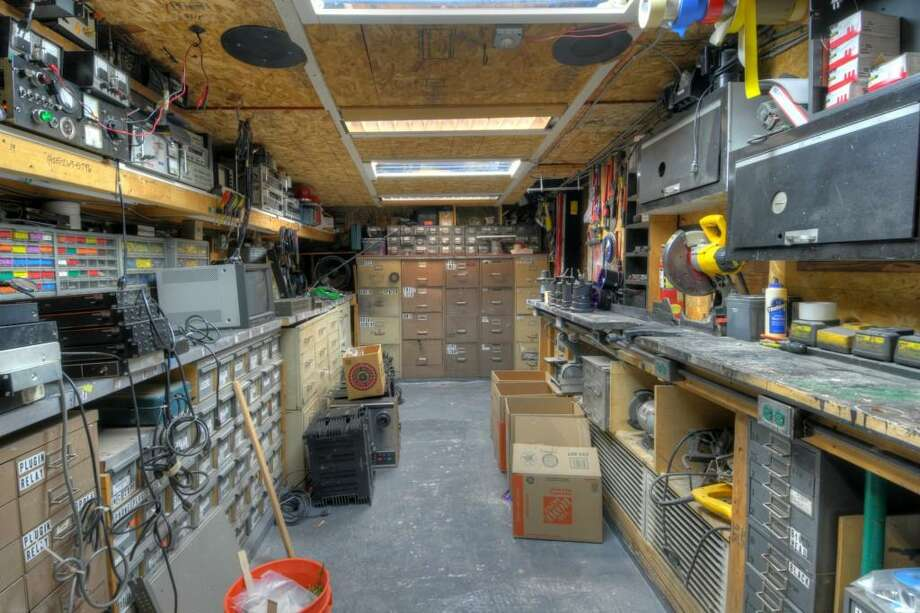 "Storeroom of 144 N.W. 103rd St., in Greenwood. The 510-square-foot house, built in 1926, has one bedroom, a three-quarter bathroom, a 16-camera surveillance system, three electrical subpanels, a gray-water well, a mirrored bedroom and wooden walkways on a 5,100-square-foot lot. It's listed for just $199,950, although the owner's ""huge collection"" of audio, lighting and electrical supplies are available for a ""small added cost."" Photo: Marc Boyd, Sound Point Real Estate LLC"