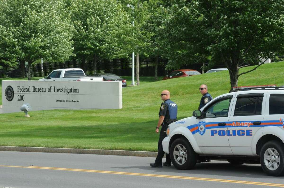 Albany police officers are stationed outside FBI headquarters in Albany on Wednesday, June 12, 2013. (Michael P. Farrell / Times Union)