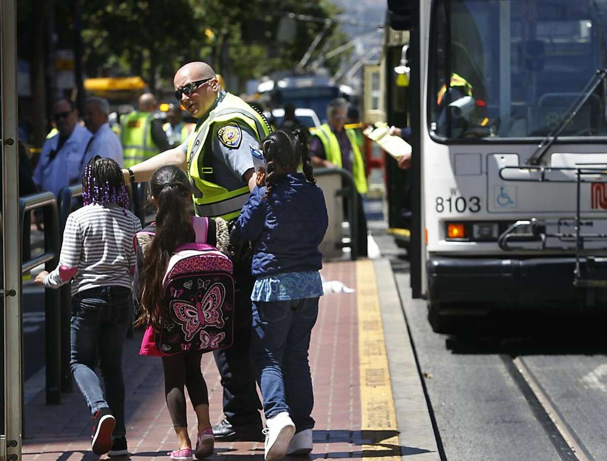 Unidentified children are escorted away from the scene after a Muni F-line streetcar rear-ended a 9L-San Bruno bus at Market and Sixth streets in San Francisco, Calif. on Wednesday, June 12, 2013.