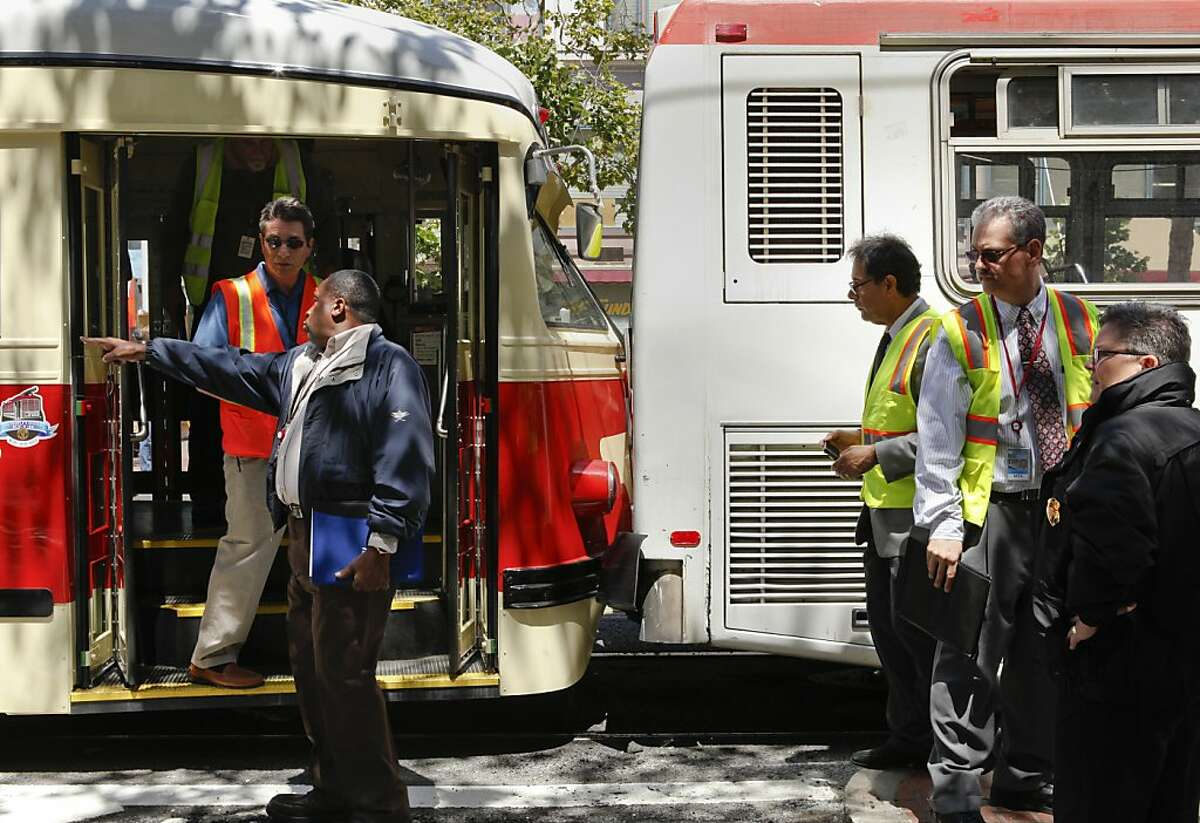 SFMTA and Muni officials work at the scene of the crash on Market and 6th Sts. in San Francisco, Calif.