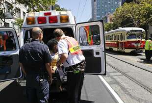 A woman is tended to at the back of an ambulance on Wednesday, June 12, 2013 in San Francisco, Calif.  A Muni F Line trolley rear-ended a Muni bus on Market and 6th Sts.