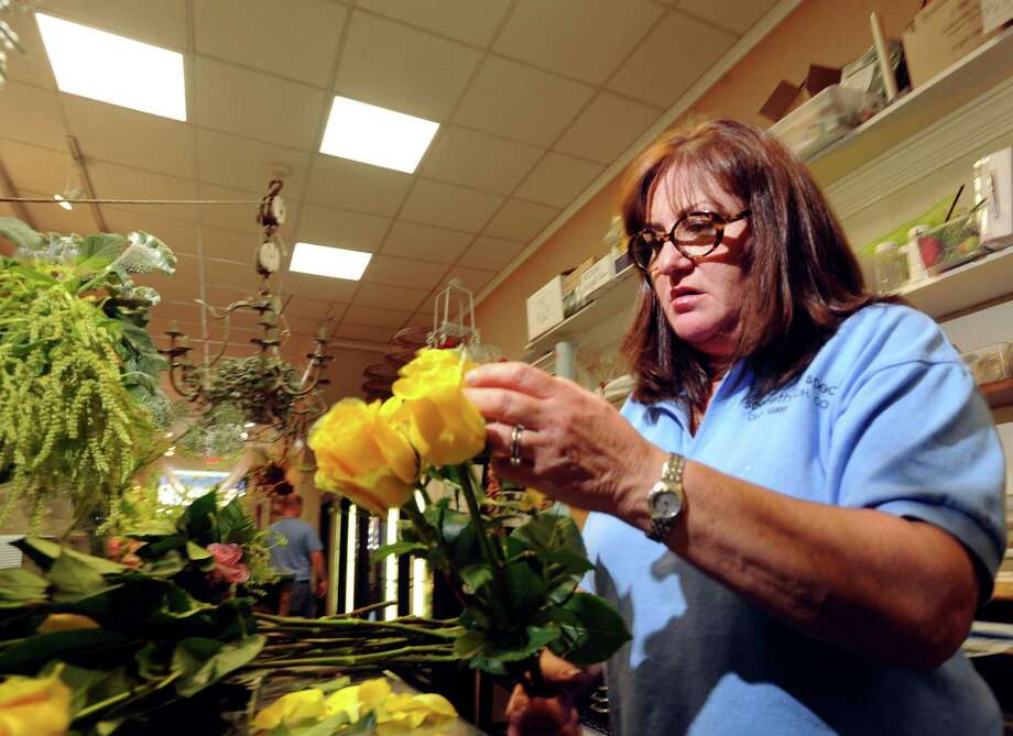 Lisa Eisenman-Salley, works with yellow roses in her flower shop, Something Special, located at 210 Sound Beach Ave., Old Greenwich, Wednesday, June 12, 2013. Photo: Bob Luckey / Greenwich Time