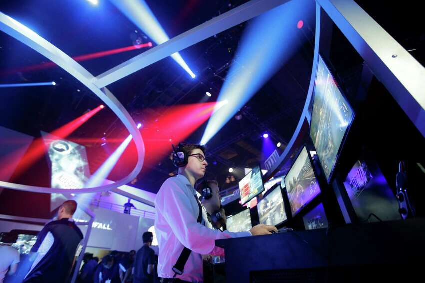 Frank Cire, center, plays the Need for Speed racing video game at the EA booth during the Electronic Entertainment Expo in Los Angeles, Wednesday, June 12, 2013. (AP Photo/Jae C. Hong)