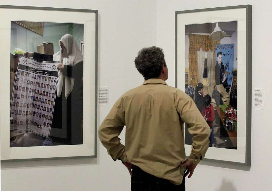 A visitor views photos by Palestinian photographer Ahlam Shibli, at the Jeu de Paume museum in Paris, Wednesday June 12, 2013. The exhibit which started last week at the Jeu de Paume, features dozens of photographs with captions that glorify dead members of Palestinian groups. (AP Photo/Remy de la Mauviniere) Photo: Remy De La Mauviniere