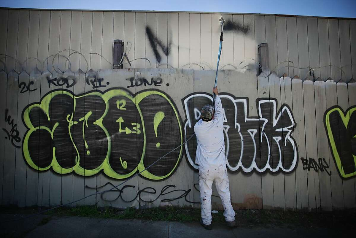 Hayward Blake, electrical painter with Keep Oakland Clean and Beautiful, uses a spray gun extension as he paints over graffiti along 12th Avenue during a demonstration on Wednesday, June 12, 2013 in Oakland, Calif.