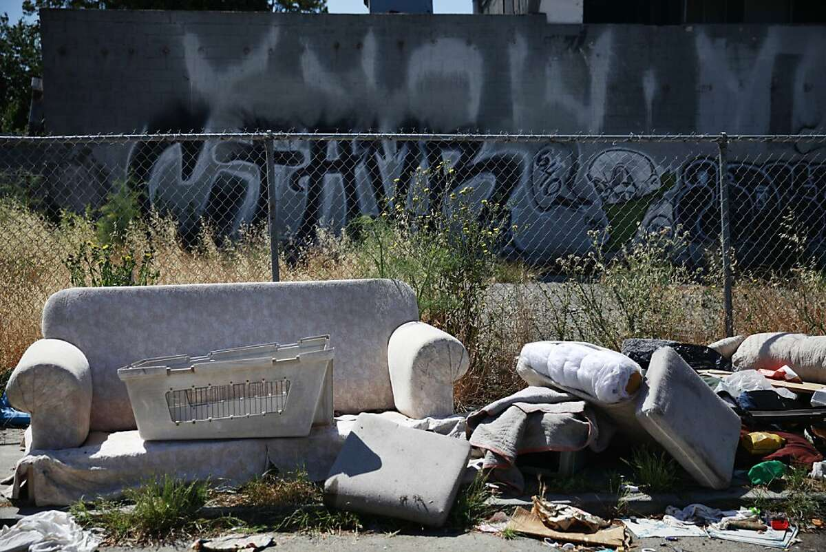 A sofa is seen along 71st Avenue near International Boulevard along with other garbage and debris on Wednesday, June 12, 2013 in Oakland, Calif.