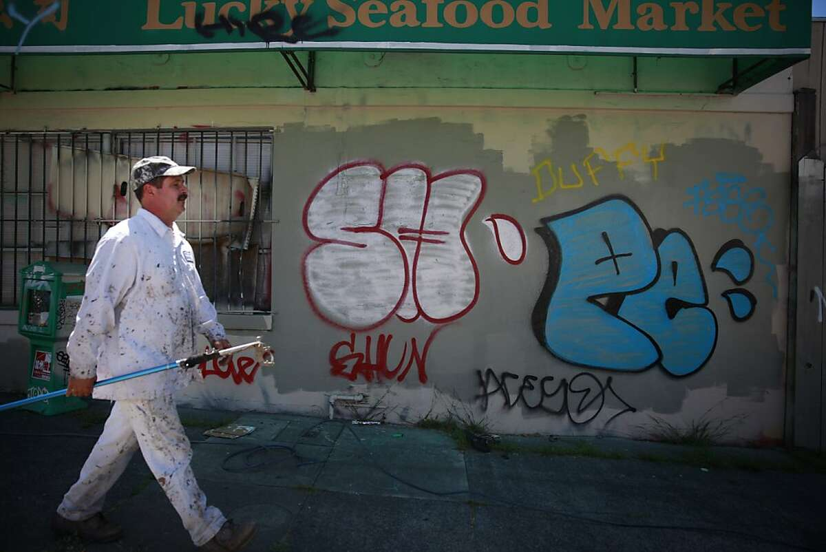 Hayward Blake, electrical painter with Keep Oakland Clean and Beautiful, carries a spray gun extension as he walks past graffiti along 12th Street before demonstrating how to paint over it on Wednesday, June 12, 2013 in Oakland, Calif.