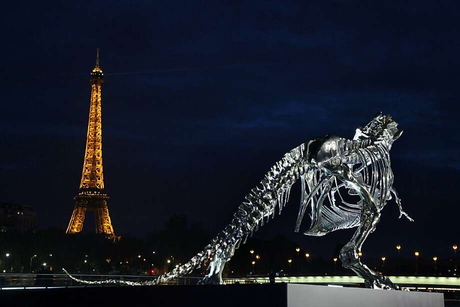Edifice, Rex:A life-size chrome-brushed aluminum skeleton of a Tyrannosaurus by French sculptor Philippe Pasqua glances back at the Eiffel Tower from a riverboat pier in Paris. Photo: Claire Lebertre, AFP/Getty Images